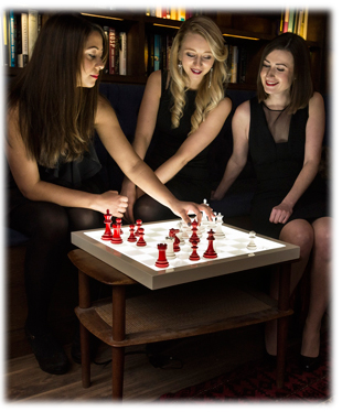 Three girls playing chess